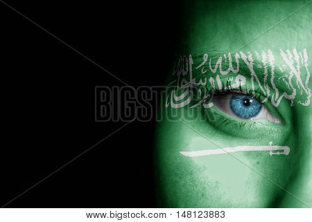 A young female with the flag of Saudi Arabia painted on her face on her way to a sporting event to show her support.