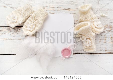 Baby New Born or baptism Greeting Card. Blank card with baby girl shoes, gloves and angel wings on white wooden background.
