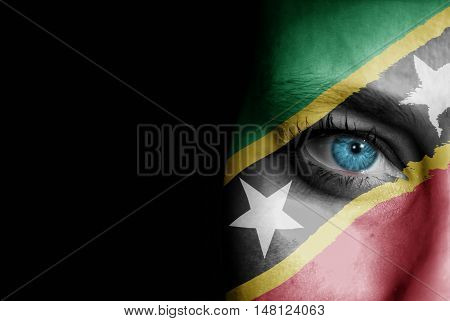 A young female with the flag of St Kitts and Nevis painted on her face on her way to a sporting event to show her support.
