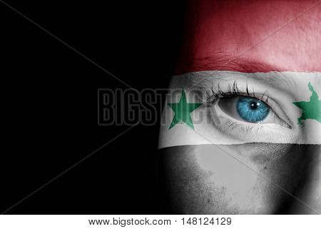 A young female with the flag of Syria painted on her face on her way to a sporting event to show her support.
