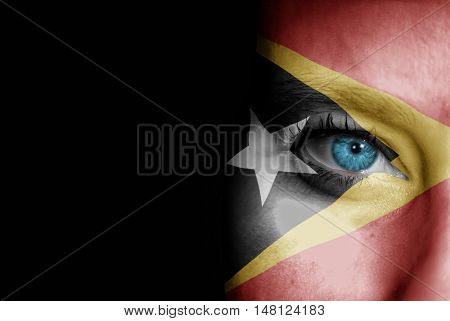 A young female with the flag of Timor Leste painted on her face on her way to a sporting event to show her support.