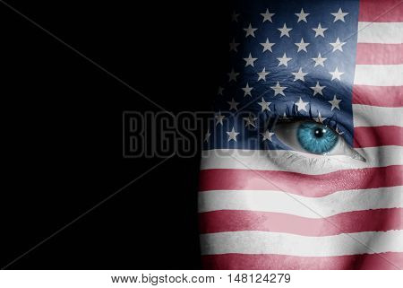 A young female with the flag of United States of America painted on her face on her way to a sporting event to show her support.