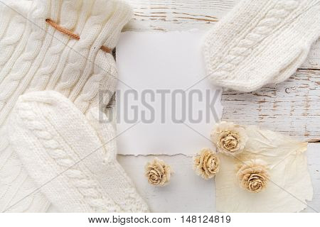 Blank card with white gloves and flowers on white wooden background. Copy space. Free space for text. Top view