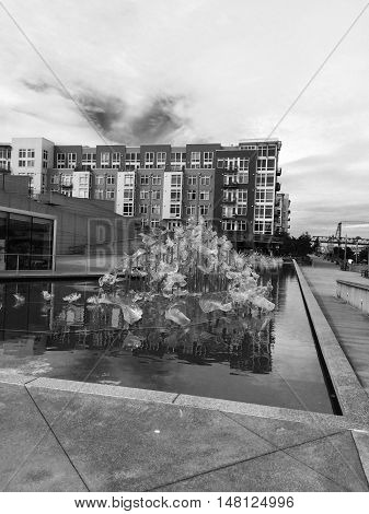Black and white photo of a fountain and building beside beside the museum of glass in Tacoma, WA