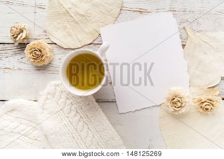 Cup of tea with gloves, white flowers and blank card on white wooden background. Copy space. Free space for text. Top view