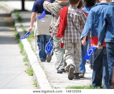 childreens group with EU flags walking ahead