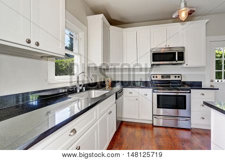 White Kitchen Room Interior With Granite Counter Top And Hardwood Floor.