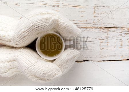 Woman's hands in gloves holding a cup of tea on white wooden background