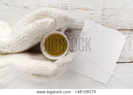 Woman's hands in gloves holding a cup of tea with blank card on white wooden background