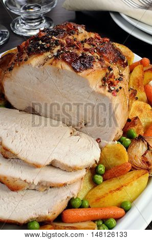 A plate of roasted turkey breast slices with vegetables closeup