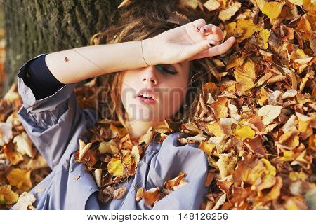 Young beautiful girl with closed eyes wearing a light gray cloak lying on a pile of autumn leaves in the Park closeup.