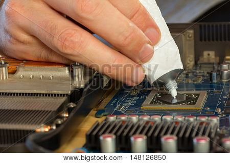 computer repair. men's fingers squeezed from a tube of thermal paste to the video processor. close-up selective focus