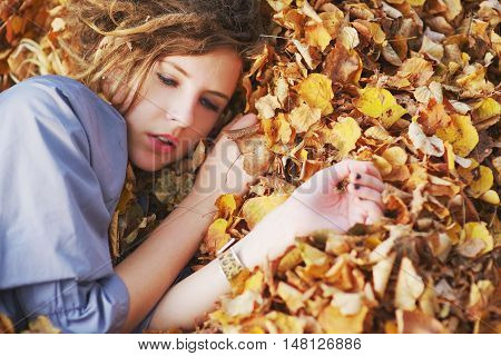 Young beautiful girl with sad eyes dressed in a light blue cloak lying on a pile of autumn leaves closeup