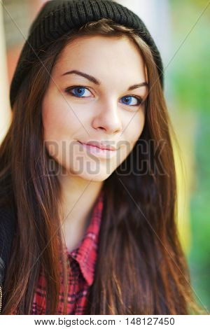 Portrait of a beautiful smiling teen girl with blue eyes wearing a red shirt and hat