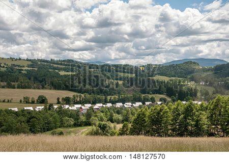 Summer landscape in a cloudy day in Jeseniky Mountains, with many new homes in Stare Mesto, Czech Republic