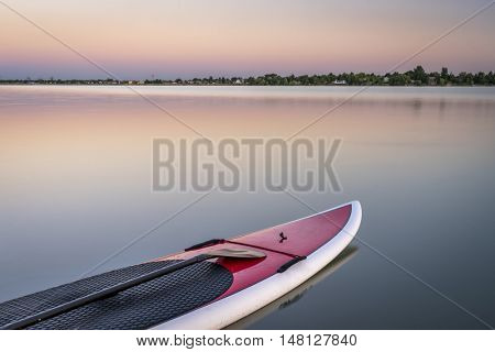 stand up paddleboard with a paddle on calm lake at dusk in northern Colorado
