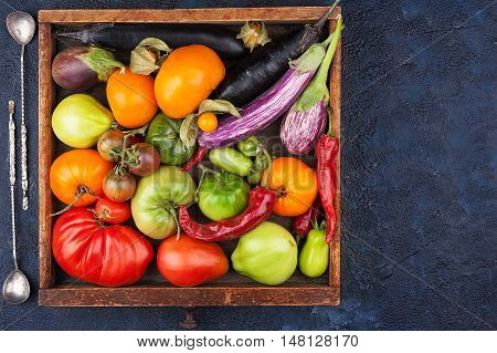 Various types of tomatoes and vegetables in a wooden box top view with copy space