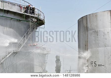 Firefighter water jet extinguish the fire started near a petrol storage tank