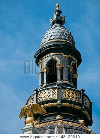Detail of the tower on a landmark building with a golden eagle on top along Meir street in Antwerp, Belgium