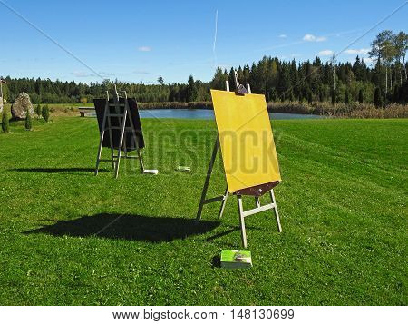 Wooden easel with blank canvas on summer green field