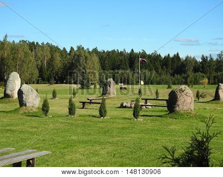 Latvian stonehenge near forest with Latvian flag.