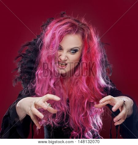Scary witch with red hair performs magic. Halloween, horror theme.