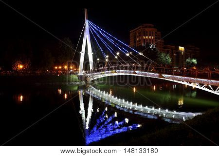 reflected night lighting of the bridge in the river. Kharkov. Ukraine