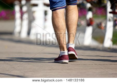 the feet of the man walking on the wooden bridge