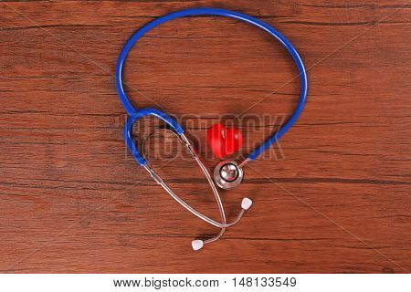 Stethoscope and red heart on wooden table