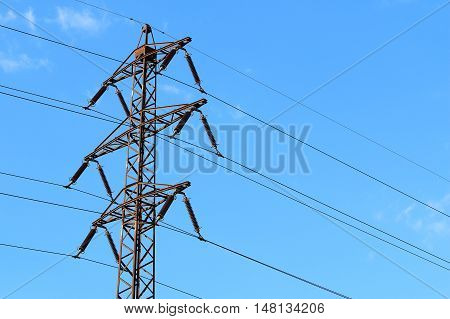 Photo of old transmission tower also power tower or electricity pylon with blue sky almost without cloud in background taken during sunny day