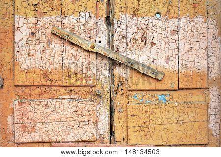 Abandoned broken wooden shed door and lock. scored plank window