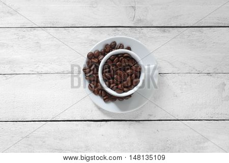 A cup of coffee beans on the center of a white wooden table. Empty copy space for editor's text.
