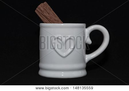 white mug with embossed heart on black background and a flaked chocolate bar