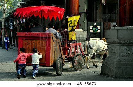 Langzhong Ancient City China - October 23 2013: Two little Chinese boys walking behind a wooden horse-drawn tourist carriage help to