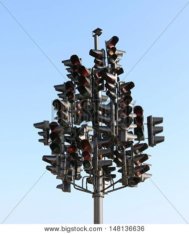 A lot of traffic lights on a blue sky background on a large crossroads