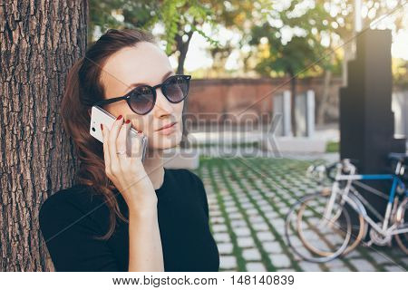 Portrait of a beautiful Caucasian woman speaking on the phone while walking in the park. Young female with ponytail and hipster sunglasses is having mobile phone conversation discussing work tasks. Copy space for your advertisement