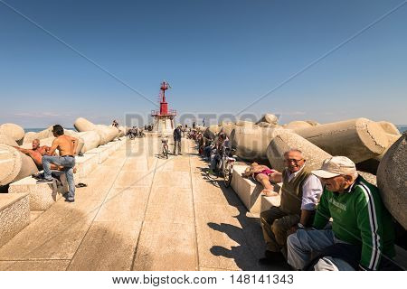Sottomarina Italy - May 20 2016: The dam lighthouse in Sottomarina (Chioggia Italy) is a meeting place for the local community.