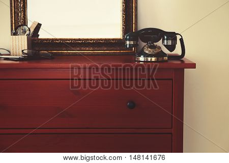 Old telephone on the chest in bedroom
