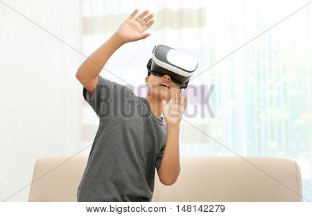 African-American boy wearing virtual reality glasses in a room