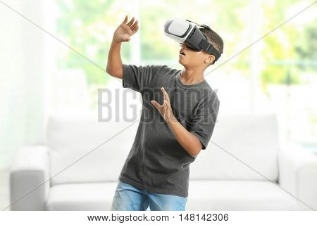African-American boy wearing virtual reality glasses on blurred window background