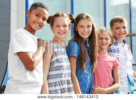 Group of pupils standing outdoors near school
