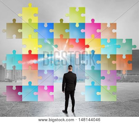 Man looks a puzzle built with colored pieces