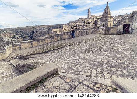 Panoramic View Of Typical Stones (sassi Di Matera) And Church Of Matera With A Couple In Love Under