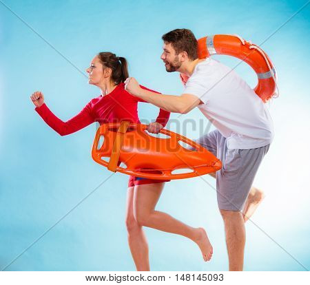 Accident prevention and water rescue. man and woman lifeguard couple on duty running with with life belt lifesaver equipment on blue