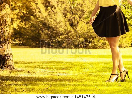 Fashion footwear beauty concept. Female legs in park. Young lady in stilettos and skirt taking walk through park.