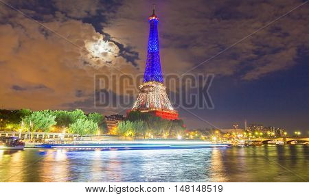 paris France-July 16 2016: The Eiffel tower lit up with the colors of French National flag to honor the victims of terrorist attack in Nice.