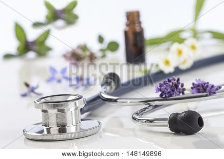 Bottle of essential oil with medicinal plant and stethoscope on white