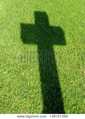 Cross casting a shadow on the grass