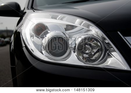 Headlight close up of black car with soft background