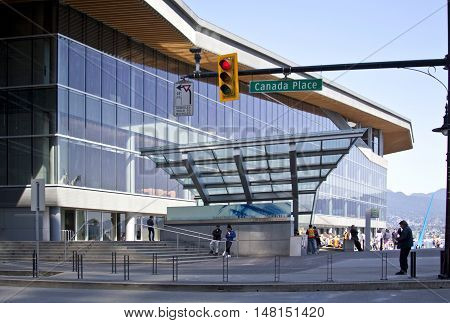 Vancouver, BC - April 20, 2015 - Full view of the Vancouver Convention Center, on a bright sunny day with blue sky. Highlights the design and art of this premier waterfront convention and exhibition facility. Many people milling about and a partial view o